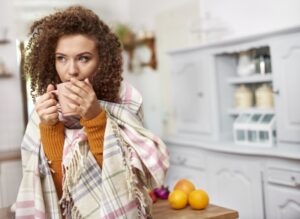 woman-huddled-in-blanket-drinking-from-mug