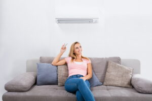 woman-sitting-on-couch-in-front-of-ductless-air-handler