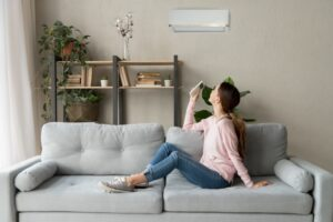woman-using-remote-to-turn-on-ductless-air-handler