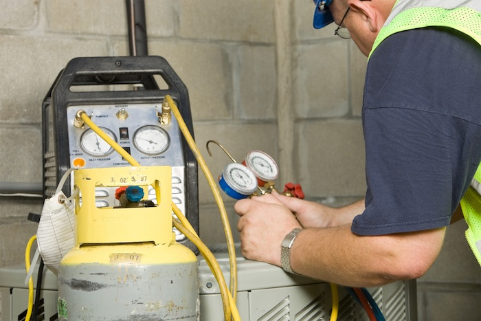 HVAC tech fixing an issue with refrigerant